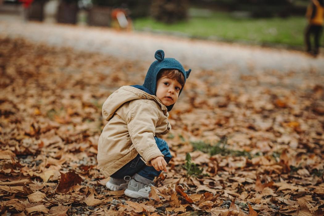 fotografia di famiglia in autunno nel parco del Valentino, bambino che gioca con le foglie secche
