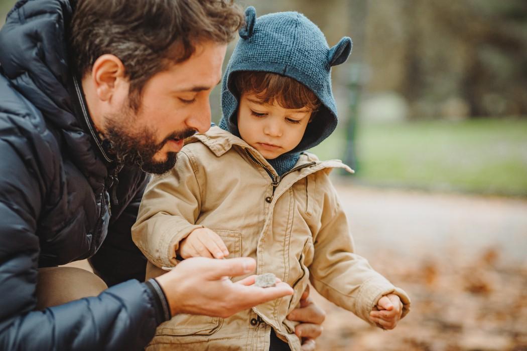 fotografia di famiglia in autunno nel parco del Valentino, bambino che gioca con le foglie secche con il papà