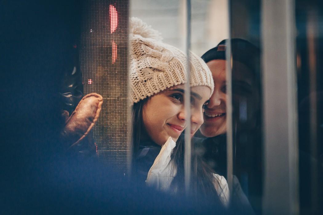 Sessione fotografica di coppia natalizia. Coppia riflessa nella vetrina di un negozio