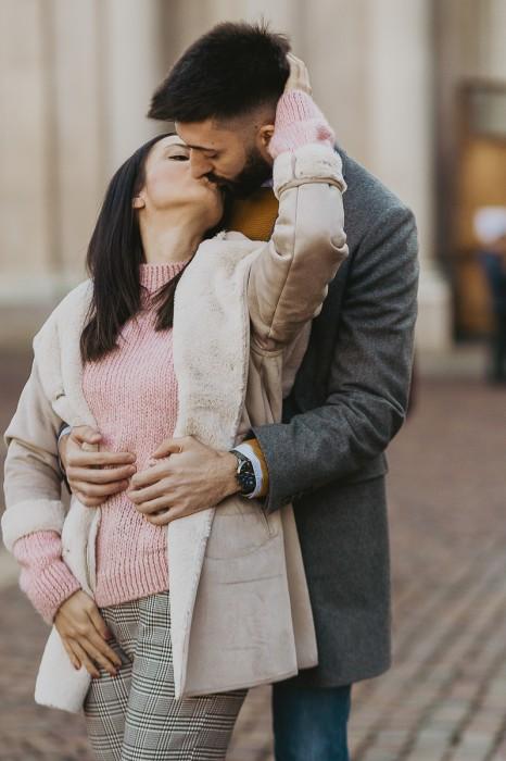 Christmas engagement session a Torino in piazza san Carlo. lei bacia lui standogli davanti