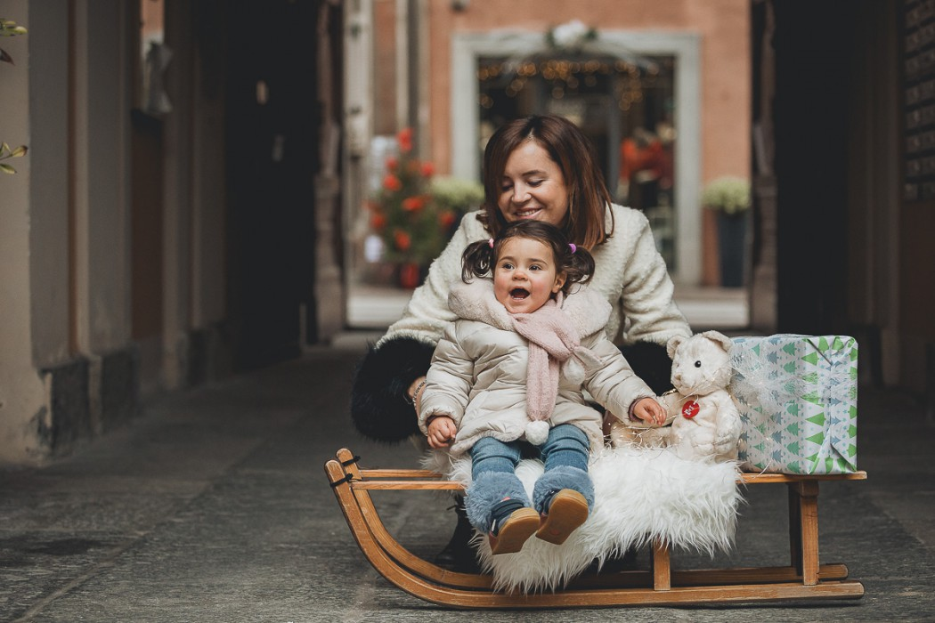 Sessione fotografica di famiglia natalizia a Chieri. Mamma papà e bambina con una vecchia slitta di legno, un orsacchiotto, pacc